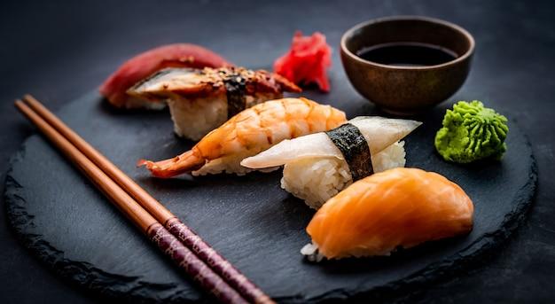Leckere sushi-sashimi-set-komposition mit garnelen-ingwer und sojasauce, serviert mit stäbchen und gr...