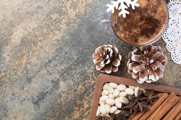 Leckere tasse kakao mit zimtstangen und tannenzapfen auf marmorhintergrund. hochwertiges foto