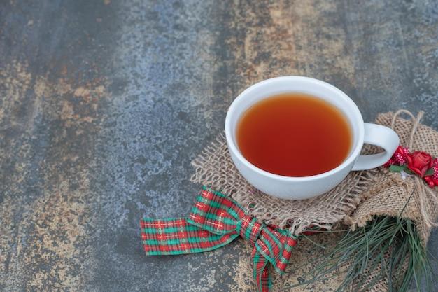 Leckere tasse tee mit schöner schleife auf sackleinen.