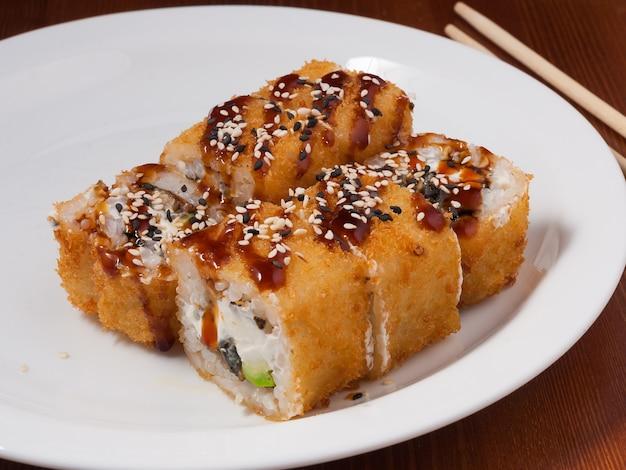 Leckere tempura-sushi-rolle mit aal auf einem weißen teller