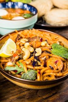 Leckere thailändische udon-nudeln mit rindfleisch; brokkoli; minze; nüsse und zitrone in der schüssel auf holztisch