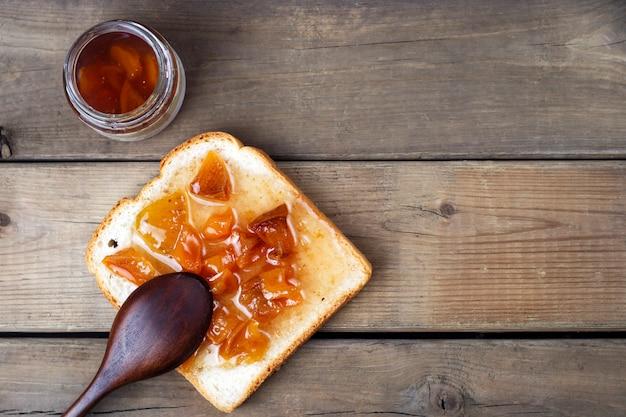 Leckere toast mit süßen marmeladen und löffel auf holz