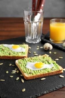Leckere toasts mit avocadopaste und gebratenem wachtelei auf schieferplatte