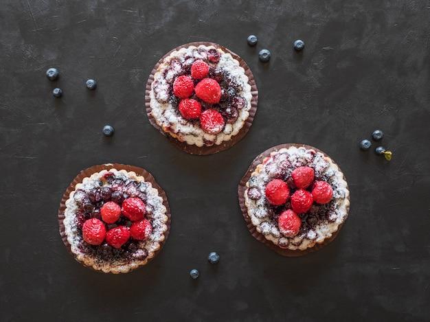 Leckere torten, bunte gebäckkuchen, süßigkeiten mit frischen himbeeren und blaubeeren