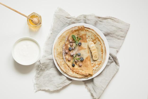 Leckere traditionelle russische pfannkuchen, sauerrahm, honig. frühling. fastnacht.