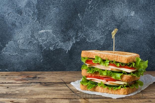 Leckere und frische sandwiches auf einem dunklen holztisch.