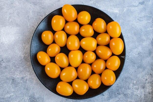 Leckere und gesunde gelbe reife tomaten auf einem teller