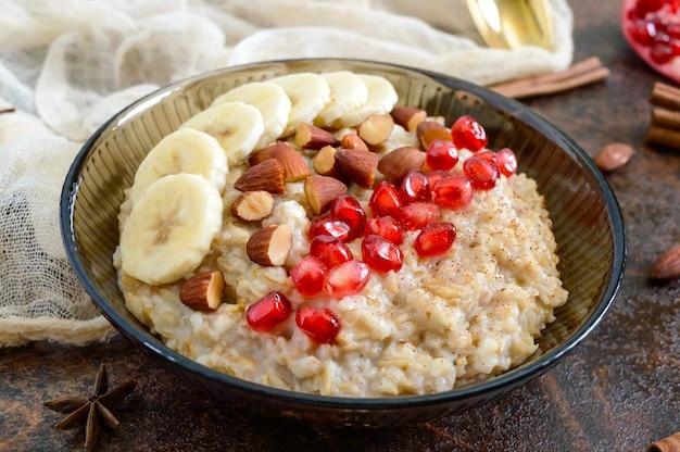 Leckere und gesunde haferflocken mit banane, granatapfelkernen, mandel und zimt. gesundes frühstück. fitness-essen. richtige ernährung.