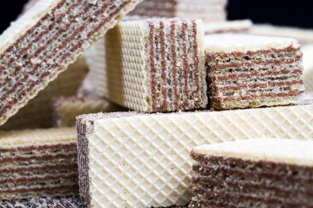 Leckere und knusprige waffeln mit schokoladenfüllung, industrieller produktion, nahaufnahme von süßigkeiten und kalorienreichen lebensmitteln