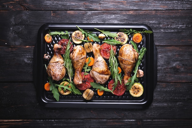 Leckere und saftige fleischstücke aus dem ofen, gegrilltes gemüse, hähnchenschenkel, abendessen für die familie