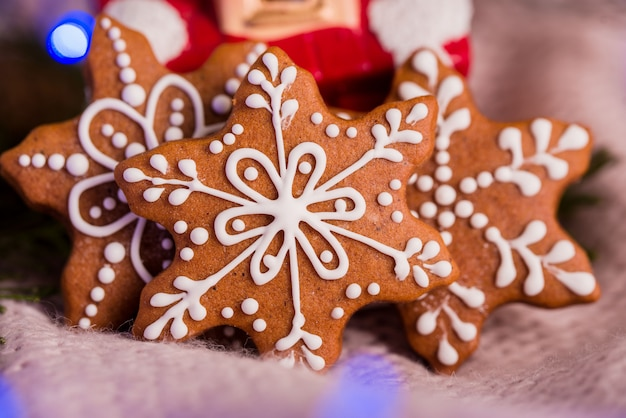 Leckere und wohlriechende schokoladenkekse werden mit puderzucker zerkleinert, mit bunten lichtern auf dem tisch. fröhliche weihnachten
