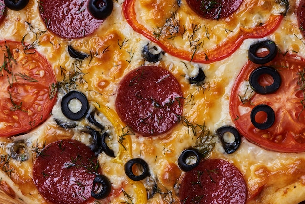 Leckere vegetarische pizza mit oliven, rotem pfeffer und tomaten. lebensmittelbeschaffenheit.