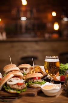 Leckere verschiedene burger und ein glas kaltes bier auf holztisch. vintage-restaurant. fastfood.