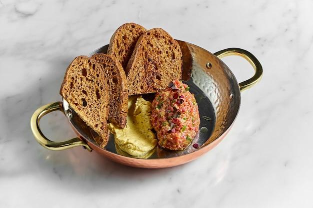 Leckere vorspeise, rindersteak-tartar mit gelber sauce und roggenbrot, serviert in einer kupferplatte auf einer marmoroberfläche