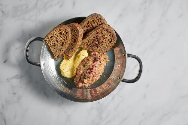 Leckere vorspeise, rindersteak-tartar mit gelber sauce und roggenbrot, serviert in einer kupferplatte auf marmor