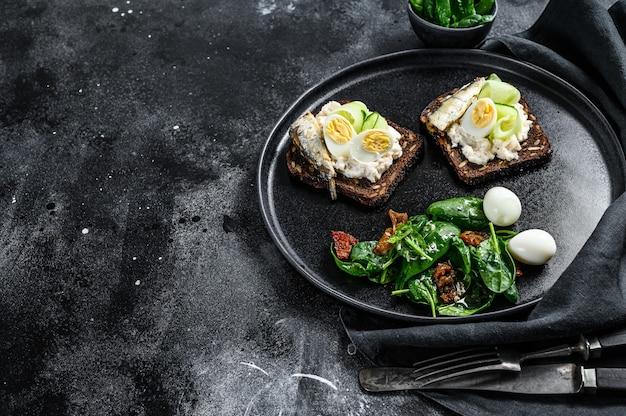 Leckere vorspeisen-tapas, weich gekochte eier und sardinen-sandwiches in dosen. salat mit spinat und getrockneten tomaten. schwarzer hintergrund.