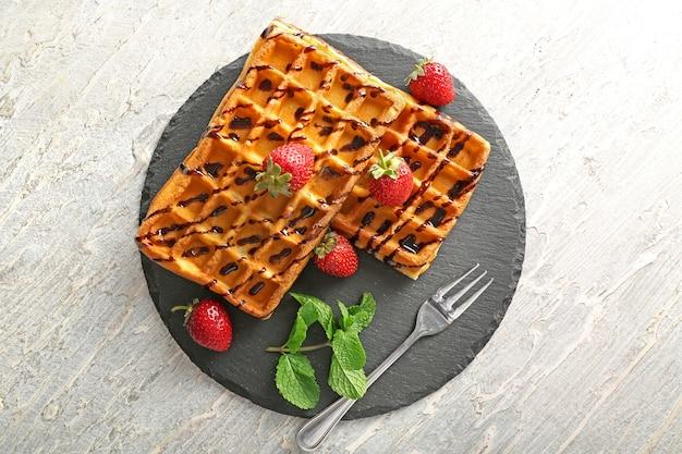 Leckere waffeln mit erdbeeren und schokoladensauce auf schieferplatte