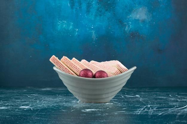 Leckere waffeln mit glänzenden weihnachtskugeln in einem weißen teller. foto in hoher qualität
