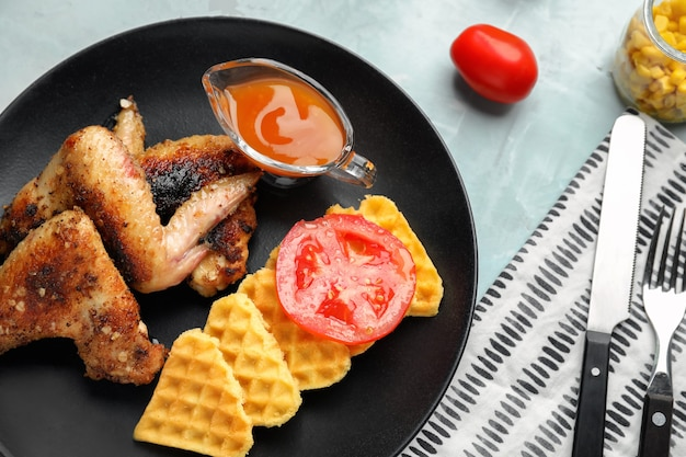 Leckere waffeln mit hähnchenflügeln und sauce auf teller