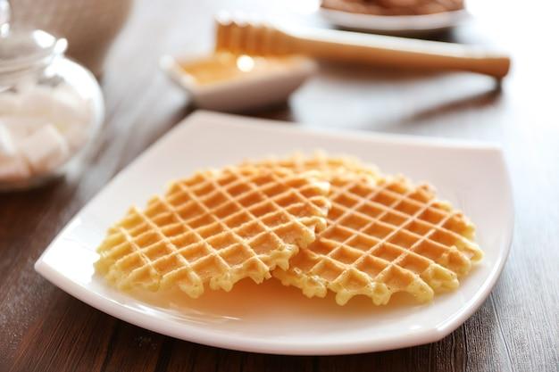 Leckere waffeln mit honig auf teller
