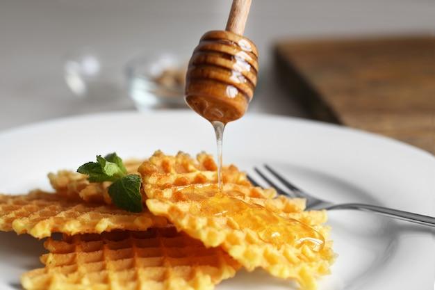Leckere waffeln mit honig und minze auf teller