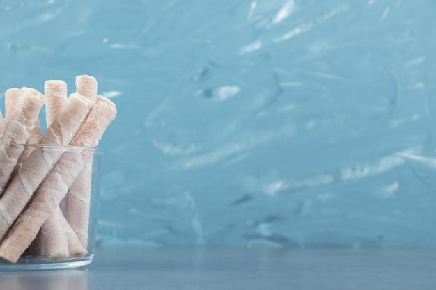 Leckere waffelröllchen in glasschüssel.