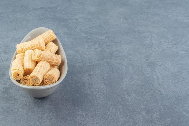 Leckere waffelröllchen in keramikschale.