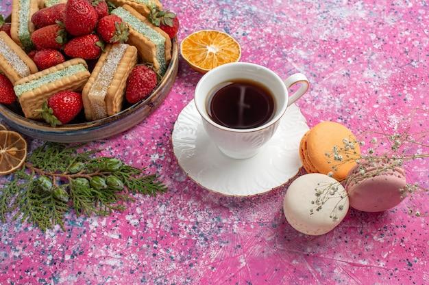 Leckere waffelsandwiches mit einer tasse tee, macarons und frischen roten erdbeeren