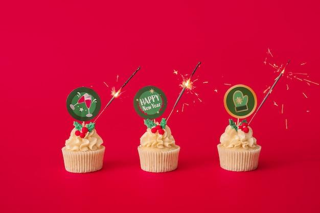 Leckere weihnachtscupcakes mit wunderkerze auf farboberfläche