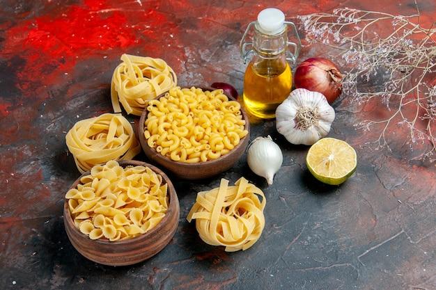 Leckere zubereitung des abendessens mit ungekochten nudeln in verschiedenen formen und knoblauchölflasche knoblauchzitrone auf gemischtem farbhintergrund