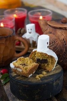 Leckereien für halloween, vorbereitung des festlichen tisches für den urlaub. orangenkürbis und muffins.