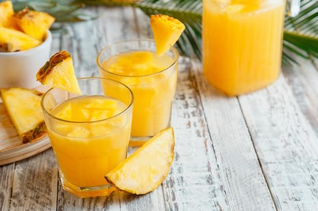 Leckerer ananassaft in zwei gläsern mit ananasscheiben. frischer natürlicher ananascocktail und saft im glaskrug auf weißem holztisch mit palmblättern. hochwertiges archivfoto