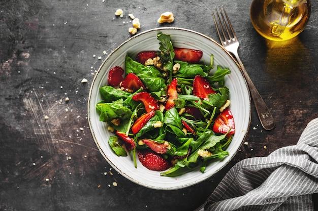 Leckerer appetitlicher, frisch zubereiteter sommersalat mit rucola, erdbeere und nüssen, serviert in einer schüssel. nahansicht