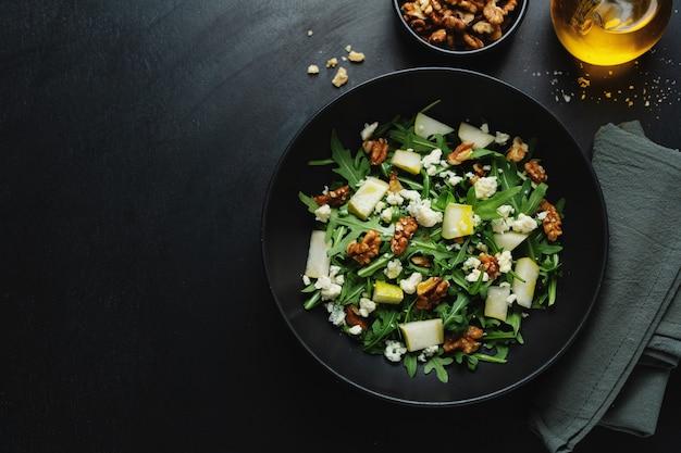Leckerer appetitlicher salat mit birne, blauschimmelkäse, walnüssen und rucola auf dunklem teller.