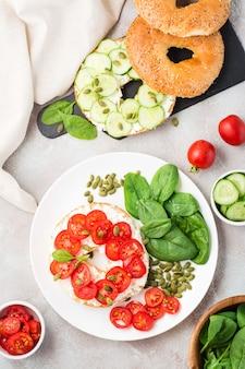 Leckerer bagel gefüllt mit feta, tomaten und kürbiskernen und spinatblättern auf einem teller. leichter gesunder vitamin-snack. vertikal- und draufsicht