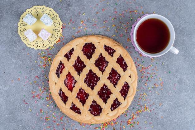Leckerer beerenkuchen, bonbons und tee auf marmoroberfläche