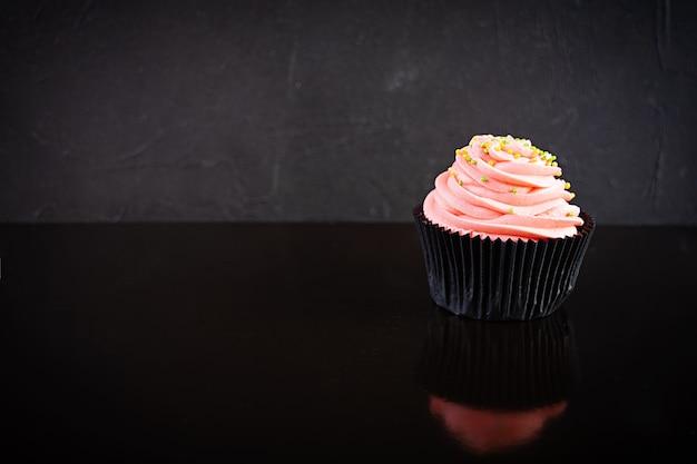 Leckerer bunter cupcake lokalisiert auf schwarz