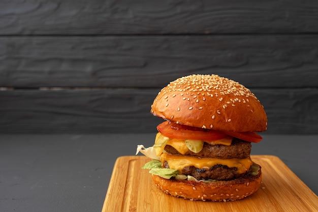 Leckerer burger auf schwarzer holzoberfläche hautnah