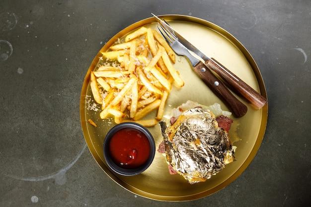 Leckerer burger-cheeseburger mit tomaten, salat und kalbskoteletts auf weißem rustikalem holztisch, nahaufnahme, selektiver fokus