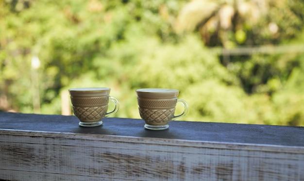 Leckerer cappuccino steht auf dem holzstrukturtisch mit naturhintergrund