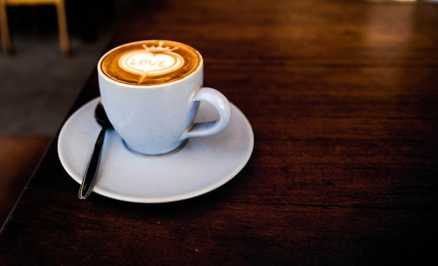 Leckerer cappuccino steht auf dem holztisch mit liebeskunst