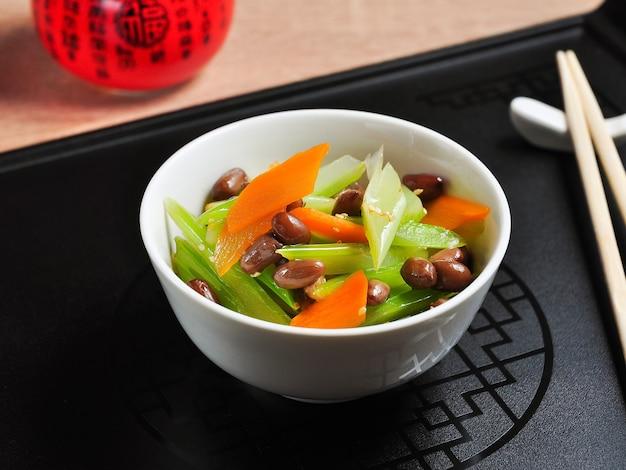 Leckerer chinesischer salat mit eingeweichten erdnüssen in einer weißen schüssel