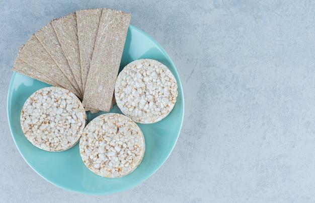 Leckerer cracker und puffreis in der platte auf marmor.