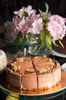 Leckerer cremiger biskuitkuchen mit karamellglasur und rosa blüten