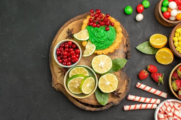 Leckerer cremiger kuchen der draufsicht mit süßigkeiten und früchten auf süßen kekskeksen des dunklen hintergrunds