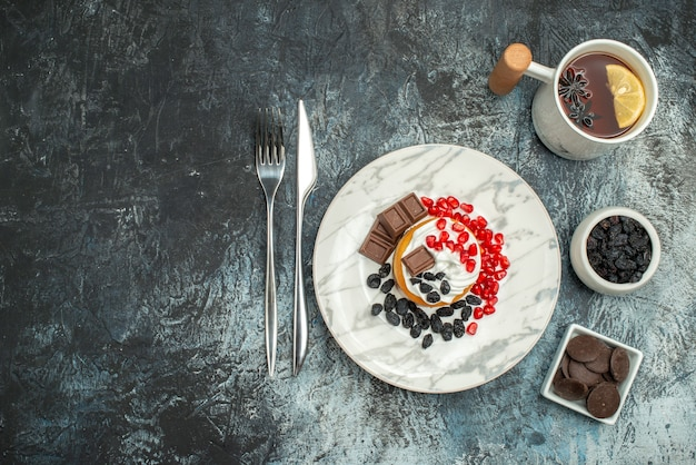 Leckerer cremiger kuchen der draufsicht mit tasse tee auf hellem dunklem hintergrund