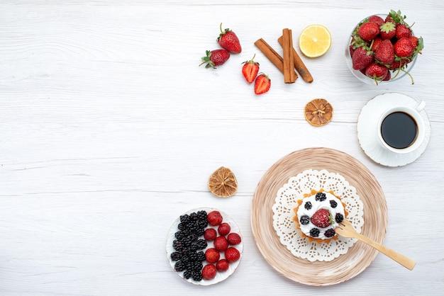 Leckerer cremiger kuchen der oberen entfernten ansicht mit beeren zusammen mit zimt-tasse kaffeekirschen auf hellem schreibtisch, kuchen süße beere