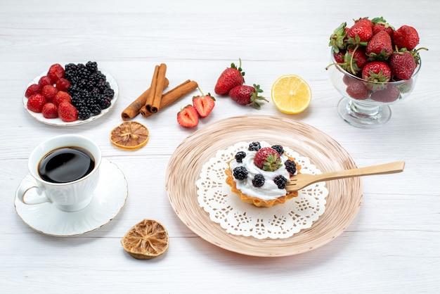 Leckerer cremiger kuchen mit beeren zusammen mit zimt-kaffee-beeren auf hellem schreibtisch, kuchen süße fotofarbe