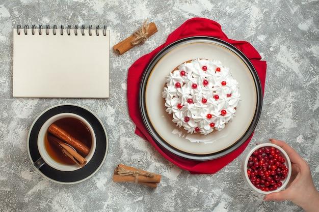 Leckerer cremiger kuchen mit früchten auf einem roten handtuch und einer tasse schwarzem tee