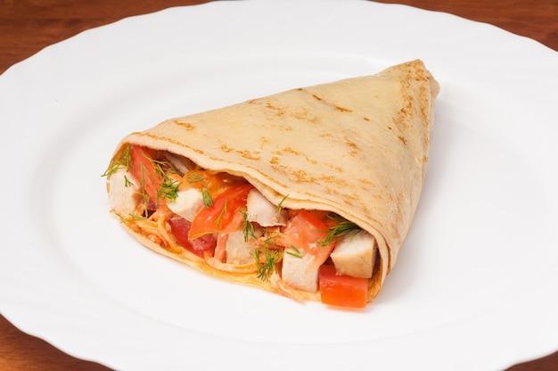 Leckerer crêpe mit tomaten und hühnchen auf einem weißen teller